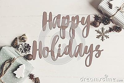 Happy holidays text, seasonal greetings card sign. flat lay. sty Stock Photo