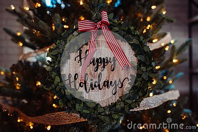 `Happy Holidays` written on a wooden decoration with red striped ribbon Stock Photo