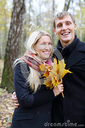 Happy husband and wife with yellow maple leafle laugh