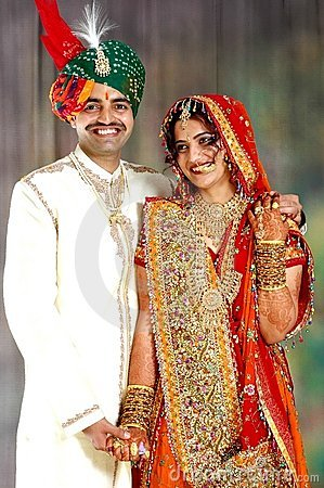Happy Indian couple in their wedding dress Stock Photo