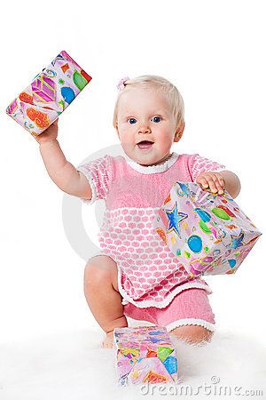 Happy infant girl with gift boxes on white