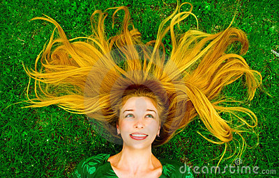 Happy joyful carefree woman with hair on grass
