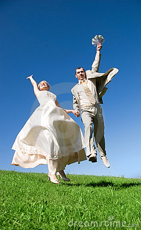Happy jumping bride and groom on the hill