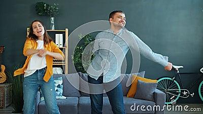 Happy junge Leute, die Spaß beim Tanzen im Haus haben und sich fröhlich und sorglos fühlen stock footage