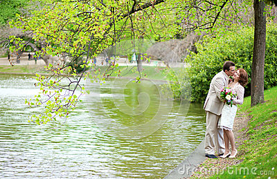 Happy just married couple in park near the water