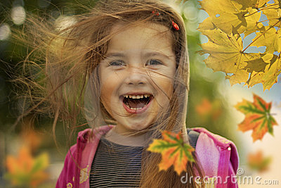Happy kid and autumn leaves
