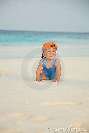 Happy kid crawling on the beach