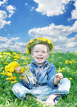 Happy kid with diadem and dandelions