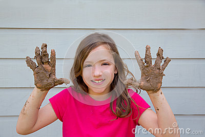 Happy kid girl playing with mud with dirty hands smiling