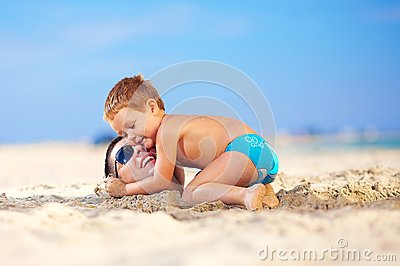 Happy kid hugging father s head in sand on the beach