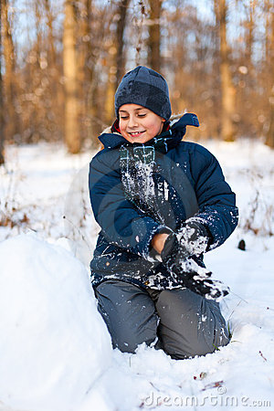 Happy kid playing in the snow