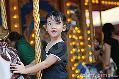 Happy kid riding a merry-go-round