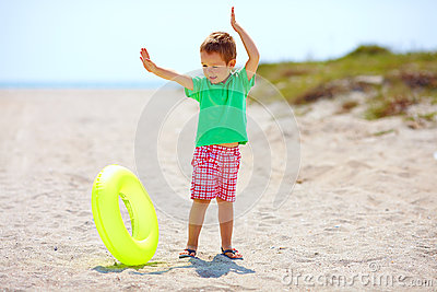 Happy kid with rubber ring on the beach