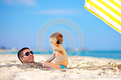 Happy kid talking on the phone, digging father in sand