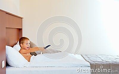 Happy kid watching tv in hotel room