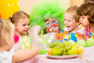 Happy kids celebrating birthday party with clown