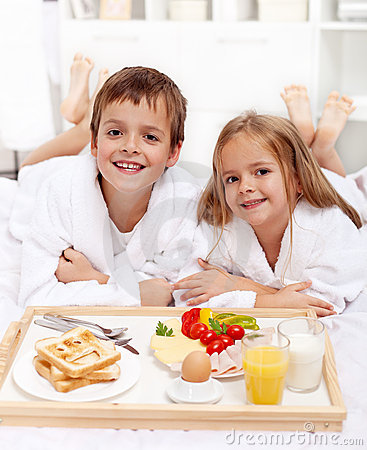 Happy kids having breakfast in bed
