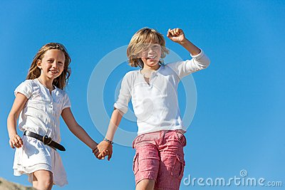 Happy kids holding hands outdoors.