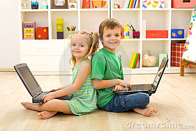 Happy kids with laptops sitting on the floor