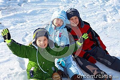 Happy kids sitting in snow