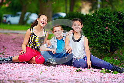 Happy kids, teenagers having fun in blooming park