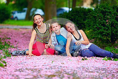 Happy kids, teenagers having fun in blooming park