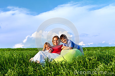 Happy kids and woman sitting outdoors