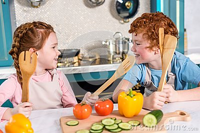 happy kids with wooden utensils smiling each other while cooking together Stock Photo
