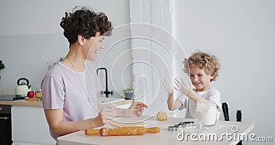 Happy Kind, das sich mit Mehl amüsieren kann und zu Hause mit Mama die Hand mit Kuchen zuhause kochen stock video