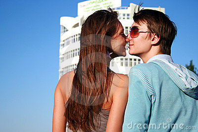 Happy kissing couple near new white building