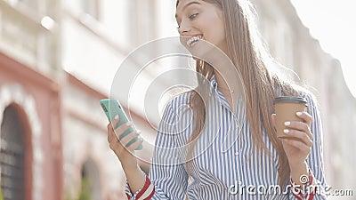 Happy Lächelnde Frau Tragen stilvolle Headband und Striping Shirt in Earphones, Holding Coffee Cup und mit ihrem Smartphone stock video footage