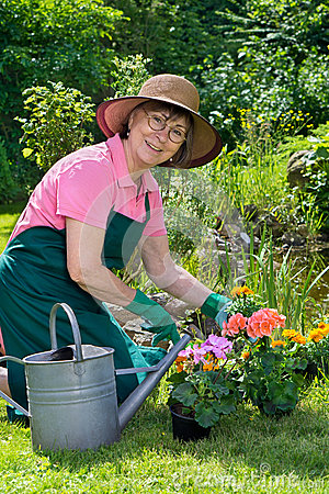 Free Happy Lady Transplanting Spring Flowers. Royalty Free Stock Photography - 56522147