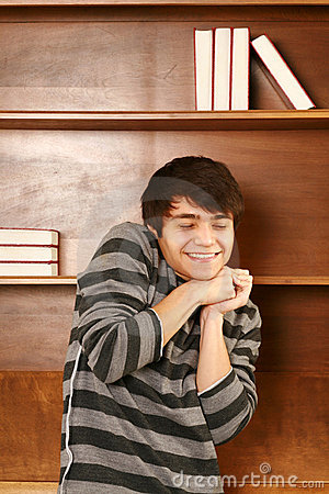 Happy latino-asian man in front of book shelf