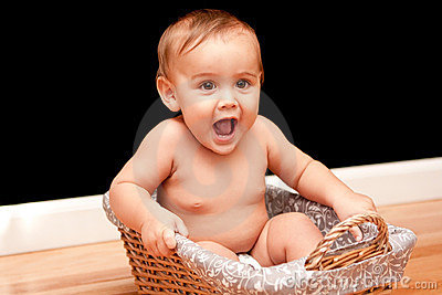 Happy, laughing 9 month old baby in basket