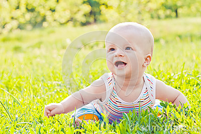 Happy laughing baby sitting on the grass