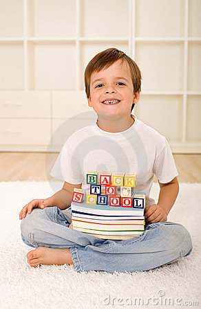 Happy laughing boy with missing tooth and books