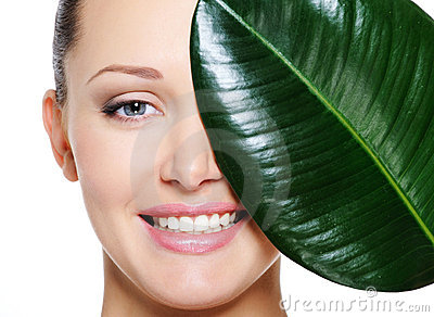 Happy laughing face of woman and large green leaf