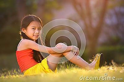 Happy little asian girl sitting on grass