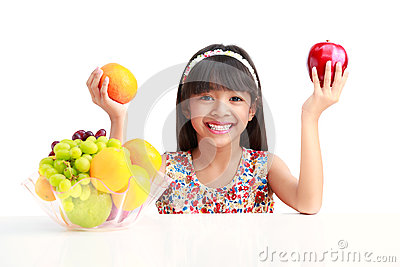 Happy little asian girl sitting on the table with plate of fruit