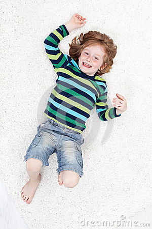 Happy little boy having fun on the floor
