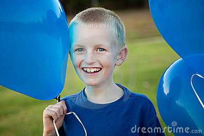 Happy little boy holding balloons