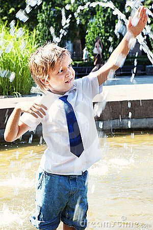 Happy little boy play in the fountain