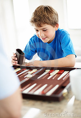 Happy little boy playing backgammon game