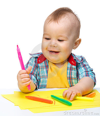 Happy little boy is playing with colorful markers