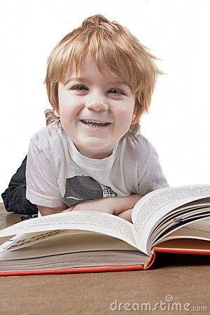 Happy little boy reading and smiling