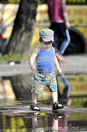 Happy little boy in vest and shorts walks on a puddle