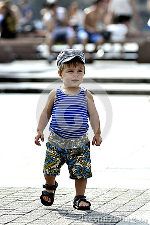 Happy little boy in vest and shorts walks on street