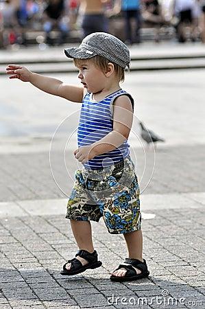 Happy little boy in vest and shorts walks on street