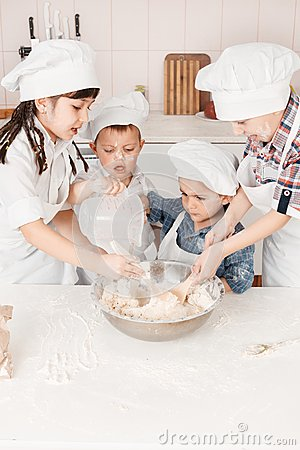 Happy little chefs preparing dough in the kitchen
