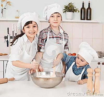 Happy little chefs preparing dough in the kitchen